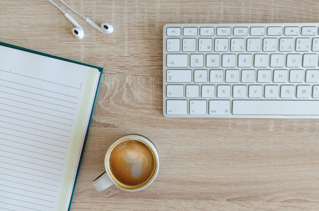 A keyboard and notebook represent the consultation, strategy, and writing in Leandra Beabout's content marketing packages.